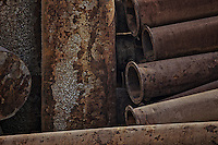 Stack of rusting drainage pipes used for tidal sediment diversion. South China Sea near Wenzhou China 2009.