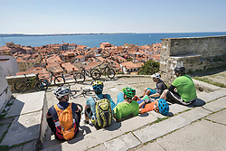 Bikers sitting on stairs and looking a congested town by sea