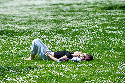 © Licensed to London News Pictures. 27/05/2021. LONDON, UK.  A woman enjoying the sunshine and warmer temperatures in St James's Park amongst the daisies after an unusually wet May so far.  The forecast for the Bank Holiday weekend is fine weather.  Photo credit: Stephen Chung/LNP
