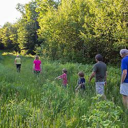A family walks a trail in Duxbury, Vermont.