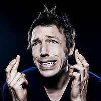 studio portrait on black background of a funny expressive caucasian man with crossed fingers hoping luck