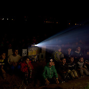 Refugee children assist to an open air cinema session set up by volunteers at the Greek-Macedonian border in Idomeni, Greece. Around 13,000 migrants and refugees, mostly from the Middle East and African nations, are believe to be stranded here awaiting a chance to proceed their journey towards Germany and other northern European countries.