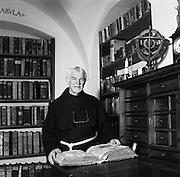 Kapuzinerpater Otho in der Bibliothek mit selbst restaurierter historischer Bibel. Père capucin Otho dans la bibliothèque du couvent de Fribourg, tenant un bible historique qu'il avait lui-mème restauré. © Romano P. Riedo