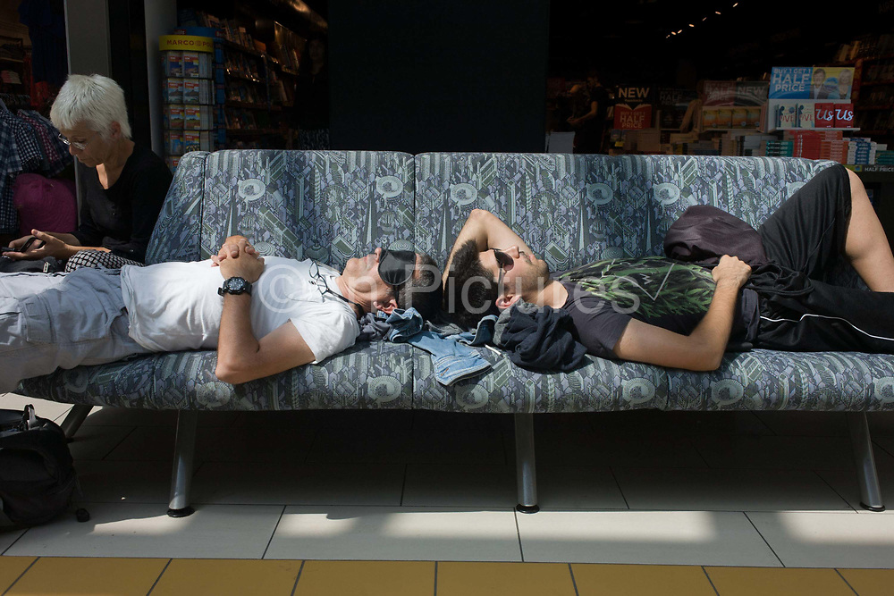Passengers stretched out on an airport terminal seat at Gatwick, London. Sleeping while waiting for their flight, the two men rest head to head on the bench in the south Terminal. According to the World Bank's data on passenger numbers carried by country, the UK carried 125,068,988 in the years 2010-14 compared the US - 762m