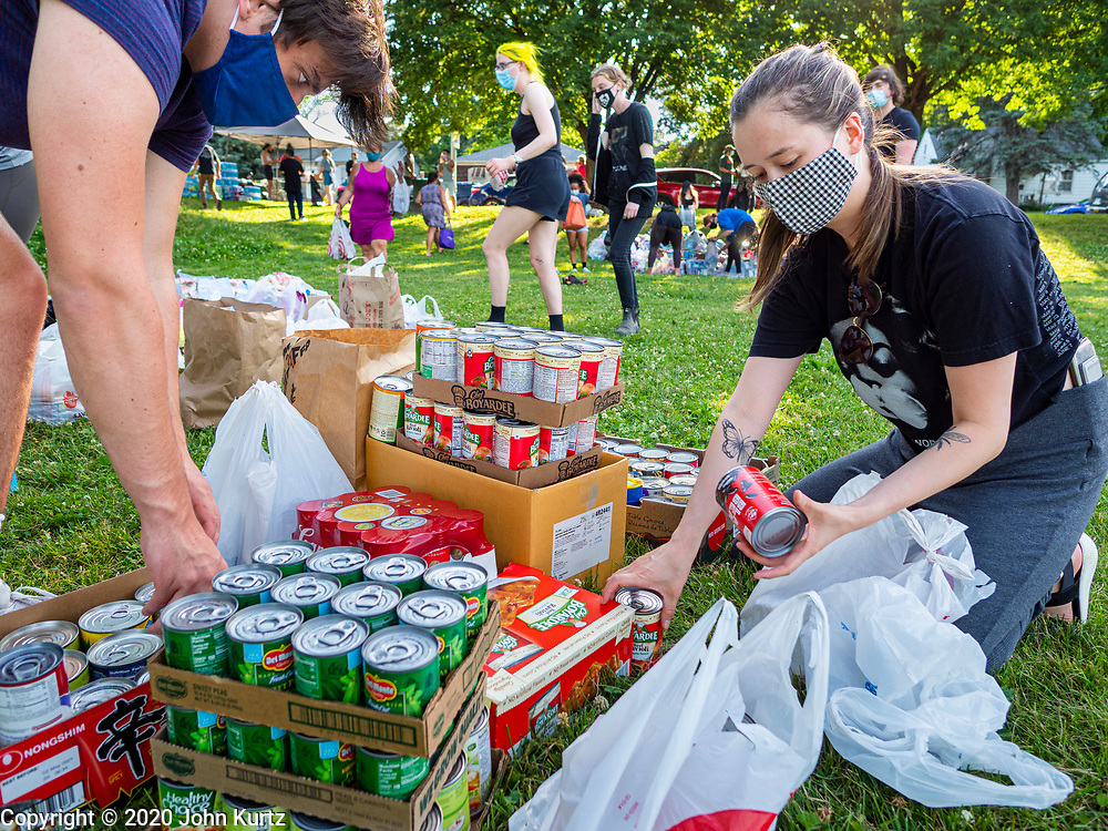 25 JUNE 2020 - DES MOINES, IOWA: Supporters of Black Lives Matter sort canned goods donated to BLM to help the homeless. Nearly 100 volunteers came to a community support event organized by Black Lives Matter in Good Park in Des Moines. They sorted supplies donated to BLM, including food, sanitary supplies, first aid supplies, batteries, blankets, tents, and bottled water. The emergency packages will be distributed to homeless people in Des Moines.       PHOTO BY JACK KURTZ