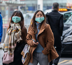 © Licensed to London News Pictures. 04/03/2020. London, UK. Two travellers walk past a taxi rank wearing masks in Westminster as top medical chief warns spread of Coronavirus is highly likely and wearing masks will not stop infections . Photo credit: Alex Lentati/LNP