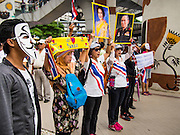 """14 JULY 2013 - BANGKOK, THAILAND:  Thai White Mask protesters hold up pictures of Bhumibol Adulyadej, the King of Thailand, (right) and his wife, Queen Sirikit during a White Mask protest. About 150 members of the so called """"White Mask"""" movement marched through the central shopping district of Bangkok Sunday to call for the resignation of Yingluck Shinawatra, the Prime Minister of Thailand. The White Mask protesters are strong supporters of the Thai monarchy. They claim that Yingluck is acting as a puppet for her brother, former Prime Minister Thaksin Shinawatra, who was deposed by a military coup in 2006 and now lives in exile in Dubai.       PHOTO BY JACK KURTZ"""