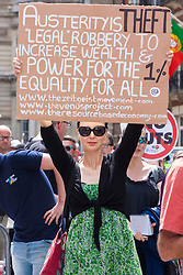 London, June 21st 2014. A woman displays her placard as thousands of anti-cuts protesters prepare to march through London.