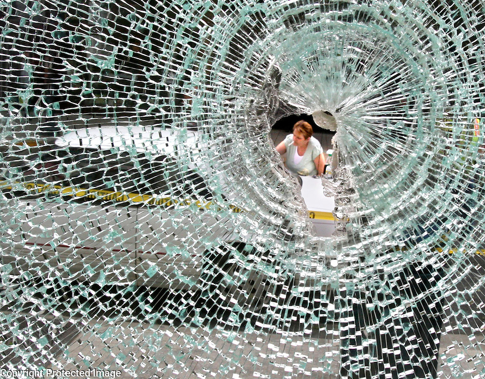 Roxie Jones is visible through a shattered window in the Rittenhouse Building in downtowntown Santa Cruz on May 2, as she tries to remove paint splattered on her car by rioters. A May Day rally turned ugly when protesters rioted, causing more than $100,000 of damage to businesses along Pacific Avenue the previous night.<br /> Photo by Shmuel Thaler <br /> shmuel_thaler@yahoo.com www.shmuelthaler.com