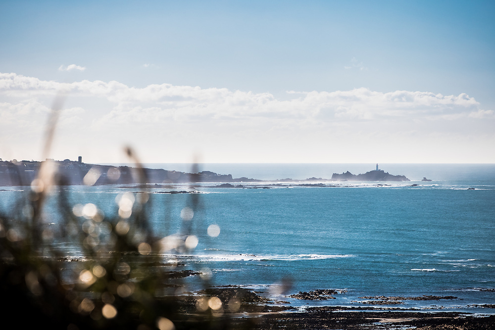 View across the sea of Corbiere lighthouse, a popular tourist destination on the west coast of Jersey, Channel Islands
