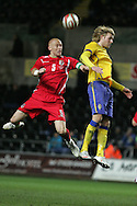 James Collins of Wales (l) challenges Sweden's Andreas Isaksson. International friendly, Wales v Sweden at the Liberty Stadium in Swansea on Wed 3rd March 2010. pic  by  Andrew Orchard