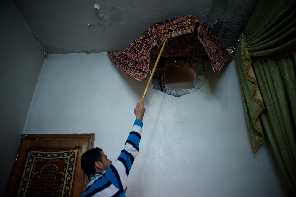 January 18, 2012 - Idleb, Syria: A local resident shows the damaged cause by government troops shelling during an attack to central Bennish.