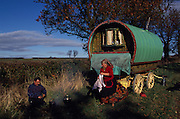 Roadside camp. Romany gypsies, Leslie and Edna traveling with a traditional bowtop wagon in the English countryside...English Romany Gypsies traditionally traveled the country roads camping nearby towns and villages, choosing the grassy roadside banks, where they tethered their horses, or in farmer's fields, when they were allowed. Travelling in bowtop wagons drawn by horses, and before that with tents, sometimes with horse drawn carts or just by foot. Often they worked as casual agricultural labourers, doing the seasons work. They also could earn their living in different ways, sometimes selling their wares, brass, tin, wood and cloth, such as embroidered cloths or lace, telling fortunes, music and dancing, and through crafts skills in basket making, plaiting chair bases, sharpening knives,  They would make fires from old wood, cleaning up after them when they moved on. There were several horse fairs, notably Appleby in Cumbria and Stow-on-Wold in the Cotswolds where they trade and sell horses, some traditions which keep to this day.