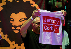 © Licensed to London News Pictures. 24/09/2016. Liverpool, UK. A man holds up a Jeremy Corbyn t-shirt. Mechanise being sold before Labour MPs and supporters celebrate  the re-elected of Labour Party Leader Jeremy Corbyn at a party organised by Momentum in Liverpool.  Photo credit: Ben Cawthra/LNP