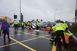Colnbrook, UK. 27th September, 2021. Insulate Britain climate activists block a slip road from the M25 at Junction 14 close to Heathrow airport as part of a campaign intended to push the UK government to make significant legislative change to start lowering emissions. The activists are demanding that the government immediately promises both to fully fund and ensure the insulation of all social housing in Britain by 2025 and to produce within four months a legally binding national plan to fully fund and ensure the full low-energy and low-carbon whole-house retrofit, with no externalised costs, of all homes in Britain by 2030.
