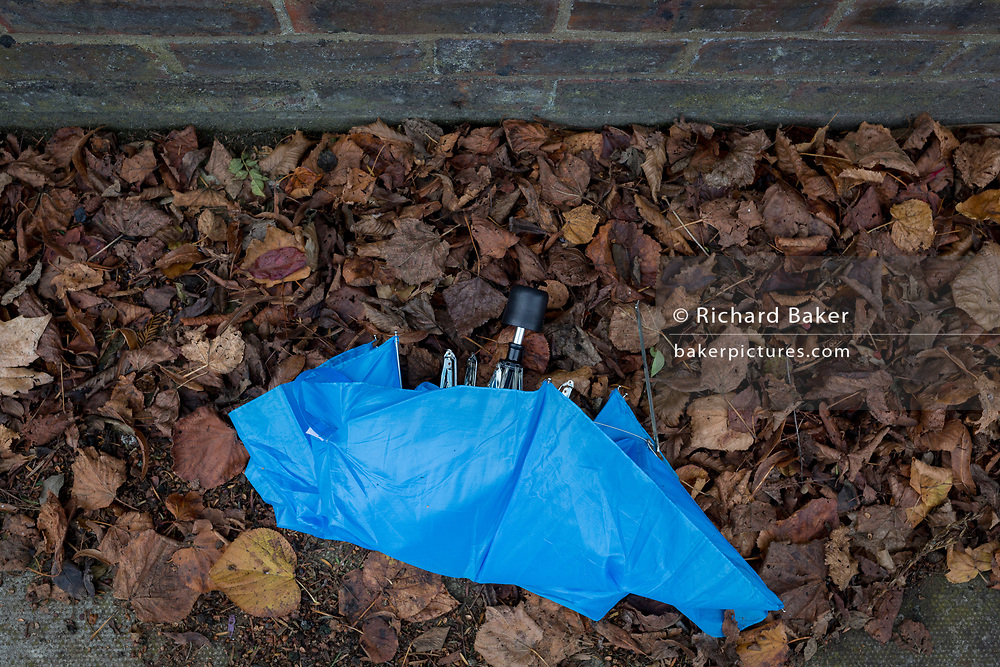 A broken umbrella lying forgotten in Autumn leaves in a residential street, on 9th November 2017, London, England.