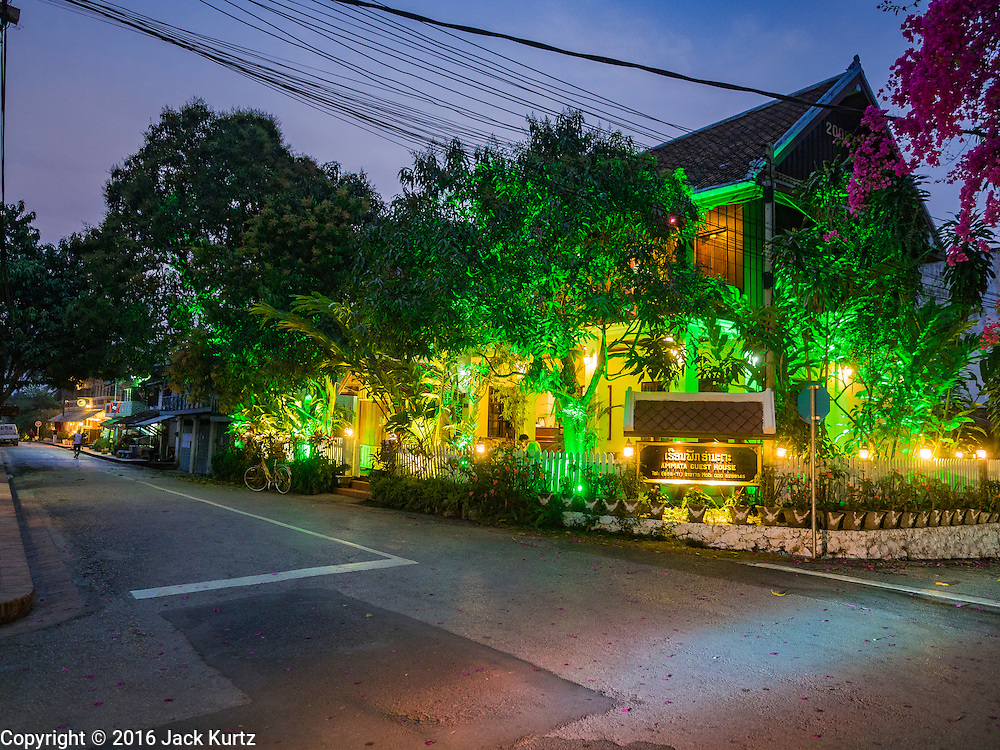 """12 MARCH 2016 - LUANG PRABANG, LAOS:  A colonial era building turned into a guest house for tourists in Luang Prabang. Luang Prabang was named a UNESCO World Heritage Site in 1995. The move saved the city's colonial architecture but the explosion of mass tourism has taken a toll on the city's soul. According to one recent study, a small plot of land that sold for $8,000 three years ago now goes for $120,000. Many longtime residents are selling their homes and moving to small developments around the city. The old homes are then converted to guesthouses, restaurants and spas. The city is famous for the morning """"tak bat,"""" or monks' morning alms rounds. Every morning hundreds of Buddhist monks come out before dawn and walk in a silent procession through the city accepting alms from residents. Now, most of the people presenting alms to the monks are tourists, since so many Lao people have moved outside of the city center. About 50,000 people are thought to live in the Luang Prabang area, the city received more than 530,000 tourists in 2014.      PHOTO BY JACK KURTZ"""