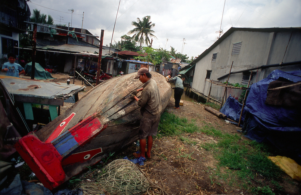 District 2 of Ho Chi Minh City, local residents work on a fishing boat, fishing being the source of income in this now disappearing area of the city due to rapid development. 2007.