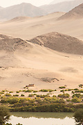 Small hut by Kunene River and mountains, Hartmanns Valley, Northern Namibia, Southern Africa
