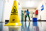 A wing cleaner mopping the floor of Beaufort House, a skill development unit for enhanced prisoners. Part of HMP/YOI Portland, a resettlement prison with a capacity for 530 prisoners. Dorset, United Kingdom.