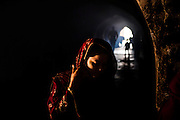 "17th December 2015, New Delhi, India. A woman in the ruins of Feroz Shah Kotla in New Delhi, India on the 17th December 2015<br /> <br /> PHOTOGRAPH BY AND COPYRIGHT OF SIMON DE TREY-WHITE a photographer in delhi<br /> + 91 98103 99809. Email: simon@simondetreywhite.com<br /> <br /> People have been coming to Firoz Shah Kotla to pray to and leave written notes and offerings for Djinns in the hopes of getting wishes granted since the late 1970's. Jinn, jann or djinn are supernatural creatures in Islamic mythology as well as pre-Islamic Arabian mythology. They are mentioned frequently in the Quran  and other Islamic texts and inhabit an unseen world called Djinnestan. In Islamic theology jinn are said to be creatures with free will, made from smokeless fire by Allah as humans were made of clay, among other things. According to the Quran, jinn have free will, and Iblīs abused this freedom in front of Allah by refusing to bow to Adam when Allah ordered angels and jinn to do so. For disobeying Allah, Iblīs was expelled from Paradise and called ""Shayṭān"" (Satan).They are usually invisible to humans, but humans do appear clearly to jinn, as they can possess them. Like humans, jinn will also be judged on the Day of Judgment and will be sent to Paradise or Hell according to their deeds. Feroz Shah Tughlaq (r. 1351–88), the Sultan of Delhi, established the fortified city of Ferozabad in 1354, as the new capital of the Delhi Sultanate, and included in it the site of the present Feroz Shah Kotla. Kotla literally means fortress or citadel."
