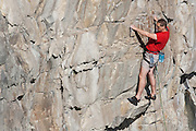 Rock climber at Dancing Ledge - a former limestone quarry on the Purbeck coast, Dorset, UK
