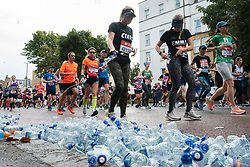 © Licensed to London News Pictures. 03/10/2021. London, UK. Partcipants run past discarded water bottles as they pass through Greenwich as part of the 2021 London Marathon.This London Marathon will be the first full scale staging of the race in more than two years due to the Coronavirus Pandemic.  Photo credit: George Cracknell Wright/LNP