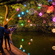 A couple strolls along the banks of Hanoi's Hoan Kiem Lake at night with colorful lights suspended from the trees overhanging the shoreline.