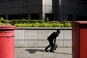 A businessman gets upright again while checking messages by an urban garden of bushes and shrubs. Seen between two Royal Mail postal boxes, this corner of urban landscape - of concrete and stone slabs - also features this area of greenery, carefully landscaped inside a wall. The male figure has stopped to attend to his briefcase while on the phone, then has got up to carry on walking towards sunshine, his shadow behind and his small briefcase in his left hand. This is the capital's financial heart - the City of London, known as the Square Mile, founded by the Romans in AD43.