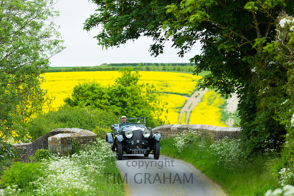 Vintage Bentley four and a half litres luxury car built in 1929 being driven on touring holiday in The Cotswolds at Asthall in Oxfordshire