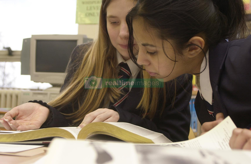Naema Badhon robh, 12 (right) from Stepney Green, and her Year 7 classmate Alexandria Eagle, 11, from Hackney, read during an English lesson at Sir John Cass Foundation and Redcoat Church of England School in Tower Hamlets, east London, on the day the 2003 GCSE tables were published, showing the school to be the secondary school with the highest value-added score in 2003 for 14 to 16-year-olds and the most improved GCSE performer for the second year running.