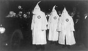 Three Ku Klux Klan members standing beside automobile driven by Klan members.  1922 March