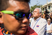 05 JANUARY 2014 - BANGKOK, THAILAND: A body guard walks ahead of SUTHEP THAUGSUBAND, leader of the anti-government movement, while he leads a march through Bangkok Sunday. Suthep is a former Deputy Prime Minister and member of the opposition Democrat Party who resigned to organize the protests against the Pheu Thai government.  He led the protestors on a march through the Chinatown district of Bangkok. Tens of thousands of people waving Thai flags and blowing whistles gridlocked what was already one of the most congested parts of the city. The march was intended to be a warm up to their plan by protestors to completely shut down Bangkok starting Jan. 13.     PHOTO BY JACK KURTZ