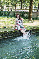 Beautiful woman splashing water with her legs at Eisbach Riverbank