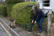 A lady with her cat outside her south London home, on 6th March 2019, in London, England.