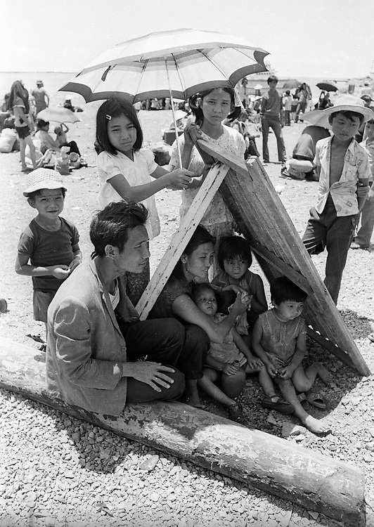 South Vietnamese refugees take a break from the hot sunshine during the evacuation of Xuan Loc, Vietnam in April 1975. Photograph by Terry Fincher