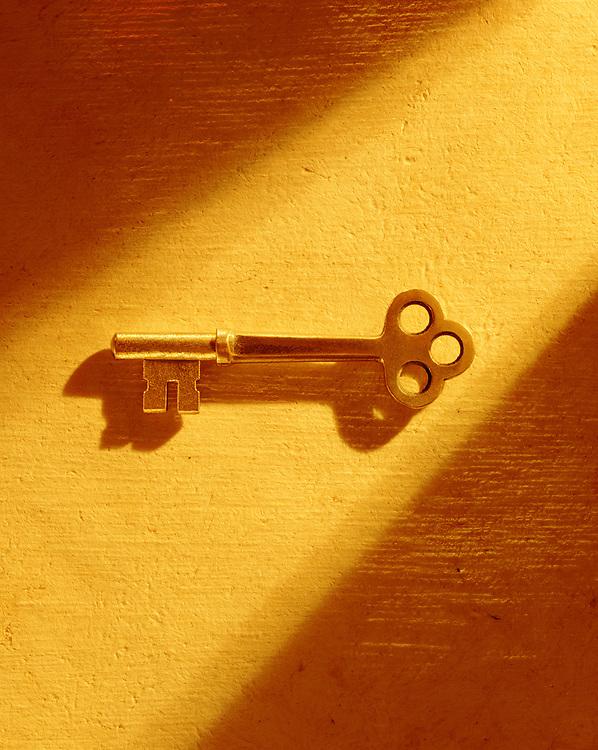 Skeleton key on textured paper illuminated by shaft of golden light