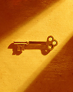 Skeleton key on textured paper illuminated by shaft of golden light
