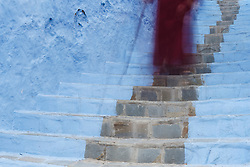 Man in red djellaba with cane on blue staircase, Chefchaouen, Morocco