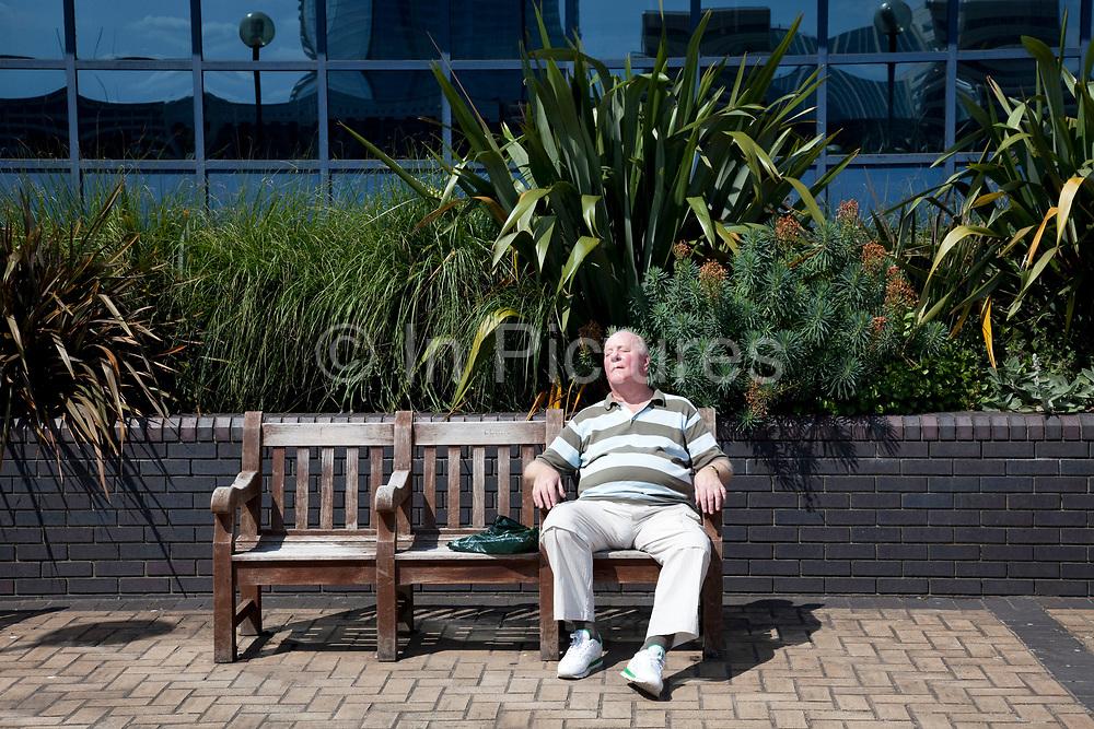Man sleeping on a bench in the sun. London.