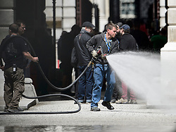"© Licensed to London News Pictures. 30/05/2015. London, UK. Water being sprayed on to the set to make it look like it has been raining. Filming for the new James Bond film ""Spector"" with Daniel Craig and Naomie Harris at the courtyard of the UK Government Treasury building in Westminster, London . Photo credit: Ben Cawthra/LNP"
