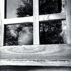 May 1970:  A clay pot sits inside of a cabin at New Salem Park in Illinois.  The trees refelct off the single pane glass window..Image taken by a pre-teen boy during the year listed in caption,  scanned and adjusted in PhotoShop.  Image was shot with a Kodak Hawkeye 126 Instamatic camera..