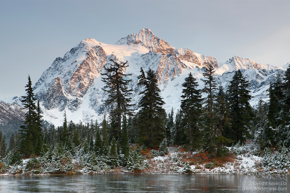 Light snow on the last traces of fall color and a layer of ice on Highwood Lake illustrate the changing seasons at Mount Shuksan in Washington's North Cascades. Mount Shuksan, located in North Cascades National Park, is 9,131 feet (2,783 meters) tall and was formed about 120 million years ago when two of Earth's plates collided and were thrust upward in an event known as the Easton collision.