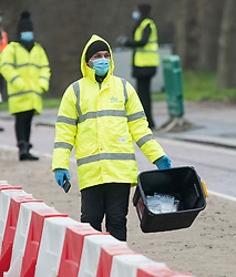 © Licensed to London News Pictures. 05/01/2021. London, UK. A worker carries a box containing completed COVID-19 tests, at a temporary drive through COVID-19 test centre in Hyde Park, central London, as the UK is placed in to a third national lockdown. Photo credit: Ben Cawthra/LNP