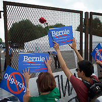 PHILADELPHIA, PA- July 25, 2016. Police officers monitor activity as activists hold Bernie Sanders campaign signs and a rose against a barricade near the Wells Fargo Center, the site of the Democratic National Convention, on the first day of events in Philadelphia, PA on July 25, 2016.  CREDIT: Mark Makela for The New York Times      NYTDNC