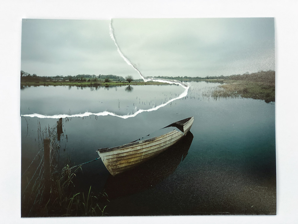 """A Sunken Boat moored to barb wire fence on the shore of the border emerges from the early morning stillness of the mirror like reflections of the River Erne. The Border follows the River Erne passed Galoon Island around Oghill into the Bloody Pass, a narrow stretch of water where 400 men died in battle in 1689. River Erne, Co.Cavan / Co.Fermanagh 54°9'17.726"""" N 7°24'27.939"""" W"""