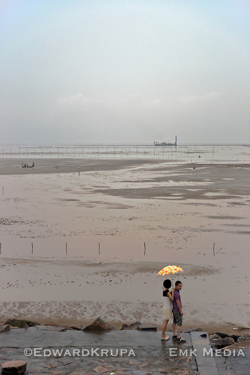 Couple taking in the evening during low tide, South China Sea.