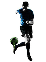 one  soccer player man juggling ball in silhouette isolated white background