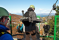 Gunstock Mountain Resort's General Manager Greg Goddard observes as Doug Klock, Adventure Park Supervisor gives the all clear to Briggs Lockwood and Doug Irving as they take on the ZipTour Mountain Zip Line Adventure Friday morning.   (Karen Bobotas/for the Laconia Daily Sun)