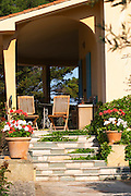 Two teak wooden deck garden chairs on the terrace and a table ready for breakfast. Flowers in pots, red and white geraniums Clos des Iles Le Brusc Six Fours Cote d'Azur Var France